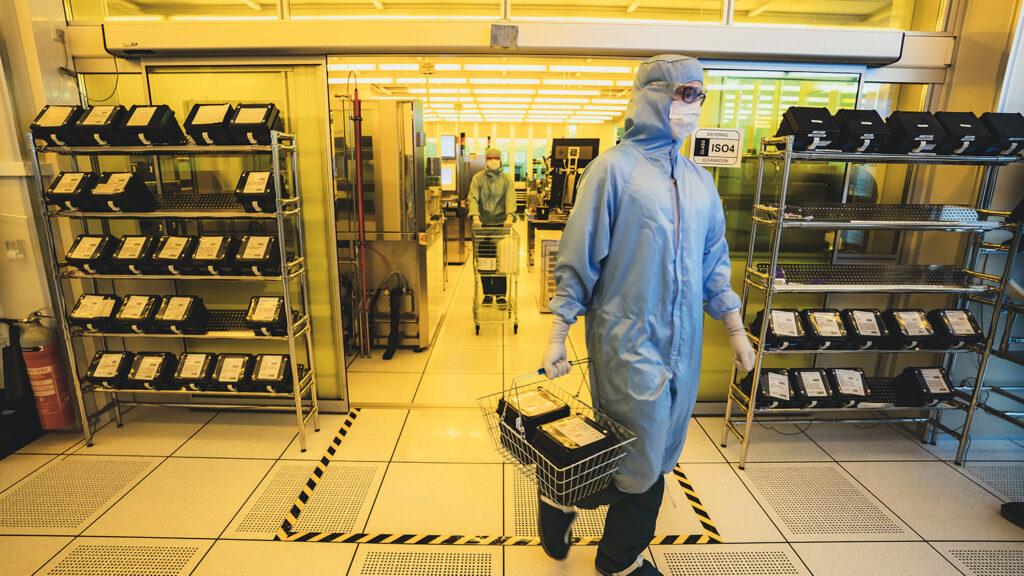 Työntekijä siirtää piikiekkoja prosessivaiheesta toiseen Muratan elementtivalmistuksessa. Takana kuljetetaan kemikaaleja.