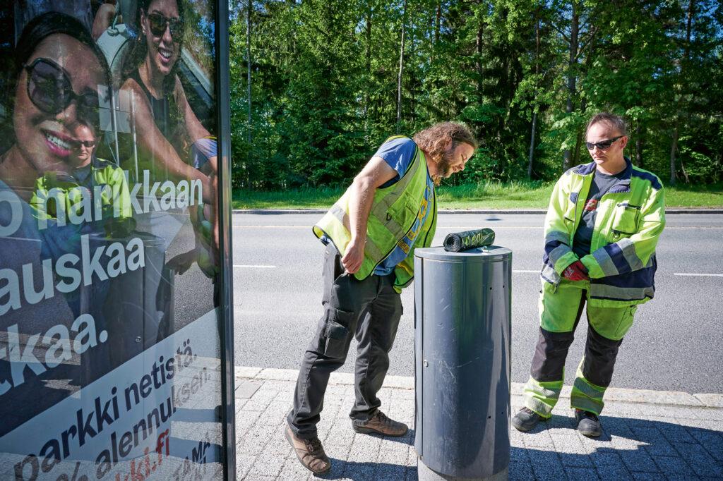 Työnjohtaja Jussi Nyman ja puistotyöntekijä Jaana Holm tarkastelevat bussipysäkin roska-astian kuntoa Espoonlahdessa Espoossa.