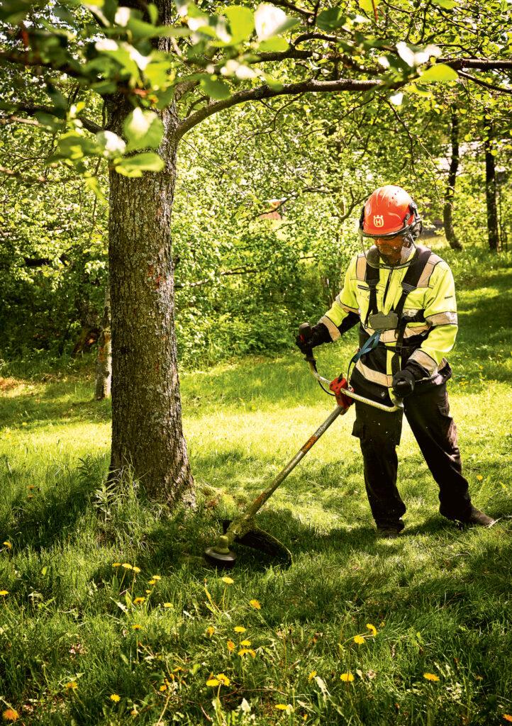 Puistotyöntekijä Deenesh Ramsahye leikkaa nurmea siimaleikkurilla Helsingin Lehtisaaressa.